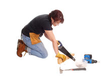 Woman working with her saw. A middle age woman kneeling on the floor and working with some tools Stock Photography