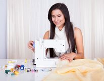 Woman working with her sewing machine Stock Images