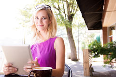 Woman working on her tablet computer at a sidewalk cafe Stock Photography