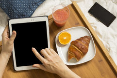 Woman working with her tablet and having breakfast Royalty Free Stock Images