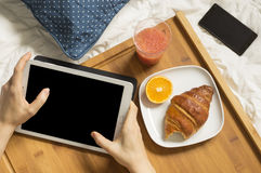 Woman working with her tablet and having breakfast Stock Photography