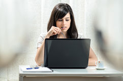Woman working at home. With a laptop while she bites the arm of her glasses Royalty Free Stock Photo