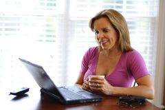 Woman working at Home Business. Woman working at home based business on computer while relaxing with a cup of coffee Royalty Free Stock Image