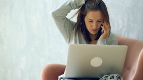 Woman working at home with laptop and talking on mobile phone