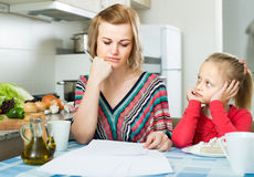 Woman working from home, little daughter asking for attention. Occupied spanish women working from home, little daughter asking for attention Royalty Free Stock Image