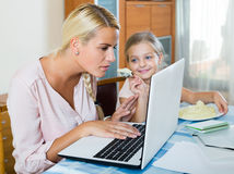 Woman working from home, little daughter asking for attention stock photos