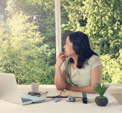 Woman working at home while looking out at bright daylight from Royalty Free Stock Image