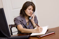 Woman working in home office. A business woman working in her home office Stock Photography