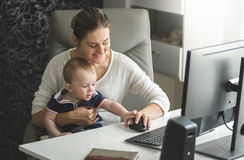 Woman working at home office and taking care of her baby son Stock Photography