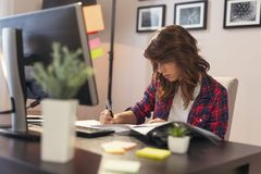 Woman working in a home office. Young woman working in a home office, signing a contract royalty free stock image