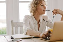 Woman working from home. Woman thinking deeply while working on laptop at home. Woman sitting at home working with laptop and diary on the table royalty free stock image