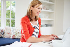 Woman Working From Home Using Laptop In Kitchen Stock Photography