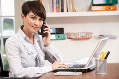 Woman Working From Home Using Laptop On Phone Stock Image
