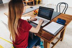 Woman working at home using laptop sitting at table in kitchen, freelancer working on notebook. stock photography