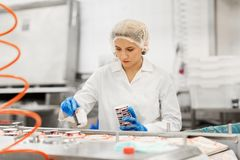 Woman working at ice cream factory conveyor stock images