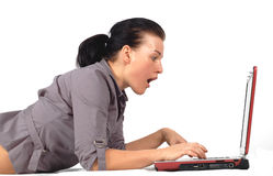 Woman working on laptop #11. Attractive brunette woman lying on white background with laptop Royalty Free Stock Photos