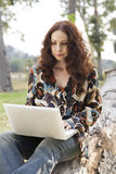 Woman working on laptop. Portrait of a middle age woman working on her laptop in a park Stock Image