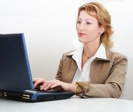 Woman working on a laptop. Close up of a smiling woman at work place Royalty Free Stock Photos