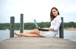 Woman working on laptop. Attractive young woman working on laptop at the water Royalty Free Stock Images