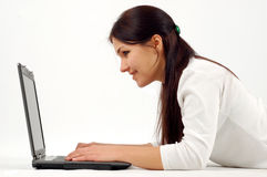 Woman working on laptop. Attractive brunette woman with laptop on white background Royalty Free Stock Image