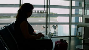 Woman working on a laptop at the airport stock video footage