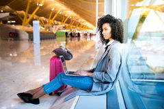 Woman working with laptop at the airport waiting at the window Royalty Free Stock Photo