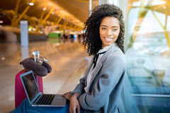 Woman working with laptop at the airport waiting at the window Stock Images