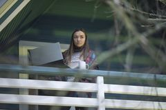 Young woman, laptop, terrace, cup of tea, nature. Woman working on a laptop on a balcony in outdoor. A woman is standing on the terrace. She threw a blanket over stock photo