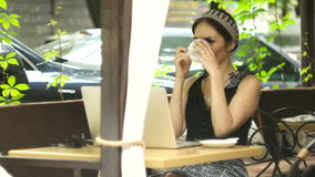 Woman working on laptop in cafe and drinking coffee, selective focus. Happy successful girl working on laptop outdoors in cafe drink coffee, selective focus stock video