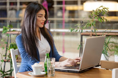 Woman working on laptop in coffee shop. Young woman in restaurant on coffee break working on lap top Stock Image