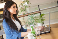 Woman working on laptop in coffee shop. Young woman in restaurant on coffee break working on lap top Royalty Free Stock Photos