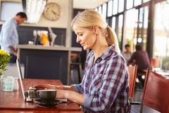 Woman working on laptop computer at a coffee shop Stock Images