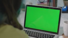 Woman working on the laptop computer with green screen at home. Chroma key. View from the back. stock video footage