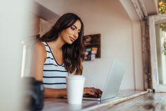 Woman working on laptop computer at home. Woman blogger using laptop at home. Woman sitting with coffee glass and camera on the table working on her laptop Royalty Free Stock Photo