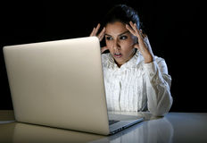 Woman working on laptop computer late at night looking stressed bored and tired Royalty Free Stock Photo