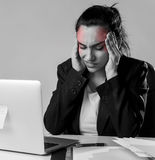 Woman working at laptop computer office desk in stress suffering intense headache and migraine Royalty Free Stock Photo