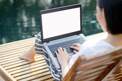 Woman working with laptop computer sitting at swimming pool. A Woman working with laptop computer sitting at swimming pool royalty free stock image