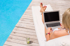 Woman working with laptop computer by the swimming pool Royalty Free Stock Photo