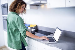Woman working on laptop while cooking Royalty Free Stock Photo