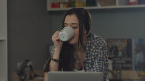 Woman working on laptop and drinking coffee at home. stock footage
