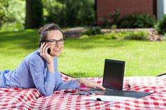 Woman working on laptop in garden Stock Photos