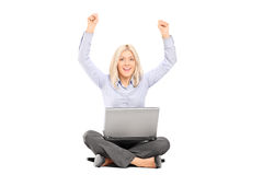 Woman working on laptop and gesturing joy Stock Photo