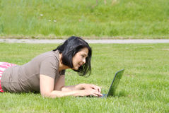 Woman working on laptop in the grass Stock Photography