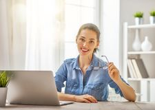 Woman working on a laptop. Happy casual beautiful woman working on a laptop at home Royalty Free Stock Photography