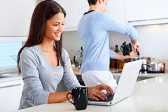 Laptop kitchen couple Stock Photos