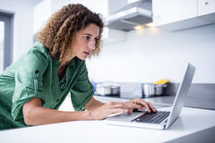 Woman working on laptop in kitchen Stock Photo