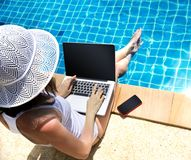 Woman working laptop near the poolside. Young woman working on laptop computer sitting at poolside stock photos