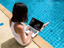 Woman working laptop near the poolside. Young woman working on laptop computer sitting at poolside stock photography
