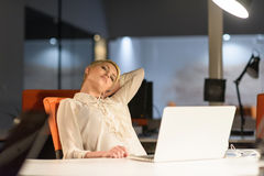 Woman working on laptop in night startup office Stock Photos