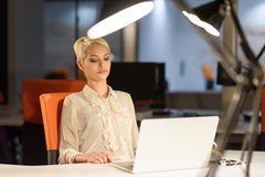 Woman working on laptop in night startup office Stock Photography